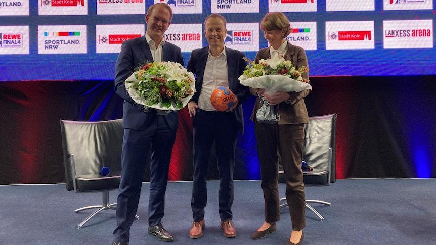 Pressetermin mit Blumen: Stefan Löcher, Frank Bohmann und Henriette Reker.