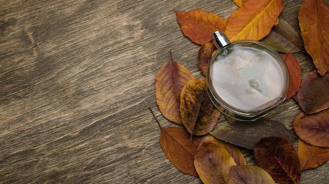 Eine Parfümflasche liegt auf Herbstlaub.