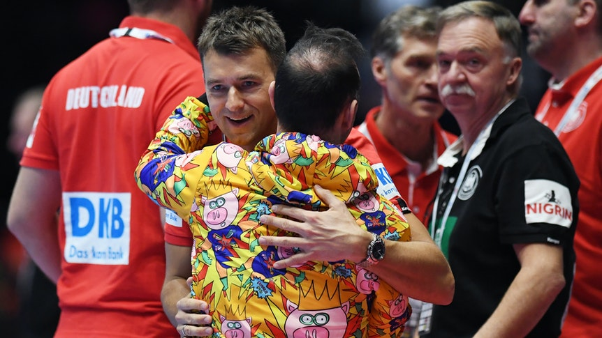 Bundestrainer Christian Prokop (l-r) aus Deutschland und Bob Hanning, DHB-Vizepräsident, umarmen sich am Ende des Spiels.