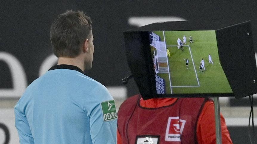 Schiedsrichter Felix Brych schaut sich in der Nachspielzeit des Bundesliga-Duells zwischen Stuttgart und Gladbach die Szene, die letztendlich zum Elfmeter samt 2:2-Ausgleich geführt hatte, auf einem Monitor am Spielfeldrand noch mal an.