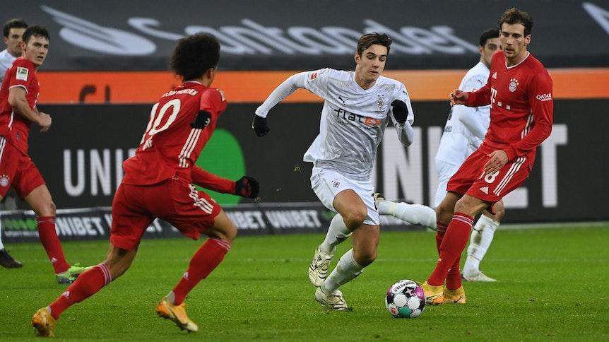 Gladbachs Nationalspieler Florian Neuhaus (Mitte) setzt sich beim 3:2-Sieg der Borussia gegen Bayern München am 8. Januar 2021 gegen Goretzka (r.) und Sane (l.) durch.