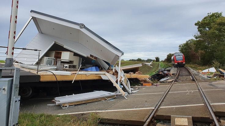 Ein zerstörtes Fertighaus liegt am Bahnübergang Sütel in Ostholstein (Schleswig-Holstein). Der mit dem Haus beladene Schwertransporter war in der Nacht zum Freitag (1. Oktober 2021) dort steckengeblieben und wurde von einem Regionalzug gerammt.