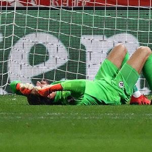Kevin Trapp von Eintracht Frankfurt wurde von einem Böller der Zuschauer getroffen und liegt am Boden.