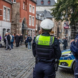 Zwei Polizisten stehen neben einem Einsatzwagen vor dem Aachener Dom.