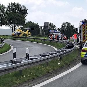 Wagen von Polizei, Feuerwehr und Rettungsdienst stehen auf einer Straße, auf der ein tödlicher Unfall passiert ist. Auch ein Rettungshubschrauber ist gelandet.