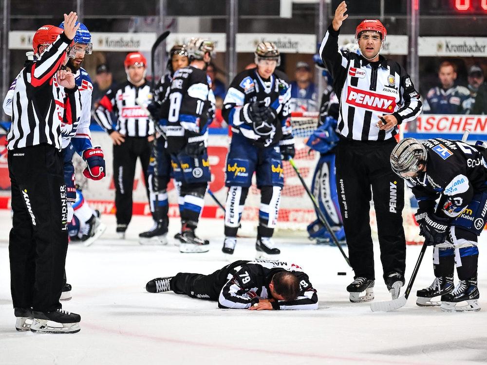 Linienrichter Andreas Kowert liegt nach einem Zusammenprall auf dem Eis.