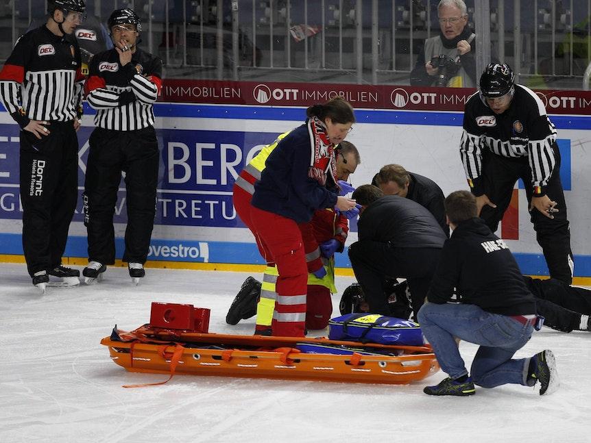 Linienrichter Andreas Kowert liegt verletzt auf dem Eis.