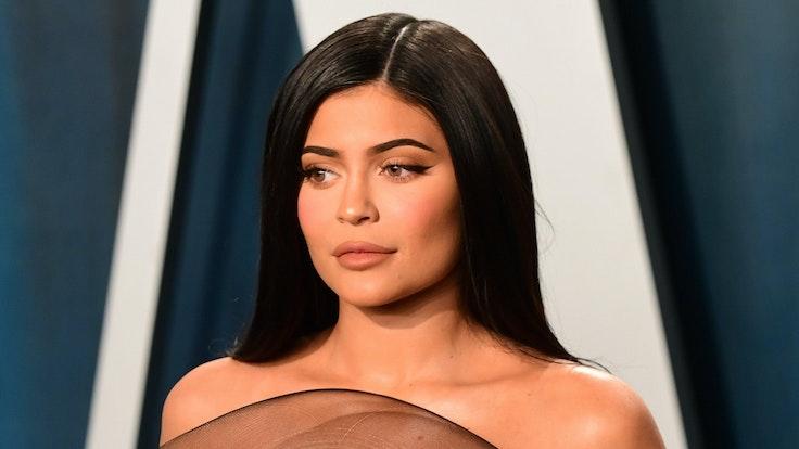 Kylie Jenner steht mit einem leichten Lächeln auf den Lippen vor einer blauen Wand.  Sie legte ihre Hände auf ihre Brüste.