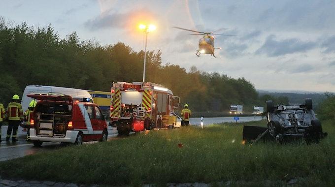 Ein Auto liegt auf der A8 auf dem Grünstreifen. Ein Rettungshubschrauber ist im Anflug.