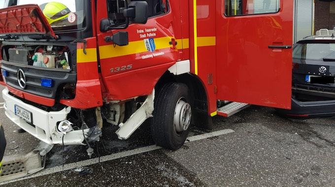 Ein Feuerwehrauto und ein ziviles Fahrzeug stehen nach einem Unfall beschädigt auf der Fahrbahn.