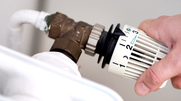 Eine Frau dreht am Thermostat einer Heizung. Die Energiepreise steigen und steigen... Womit hat das zu tun? Was kann die EU dagegen tun?