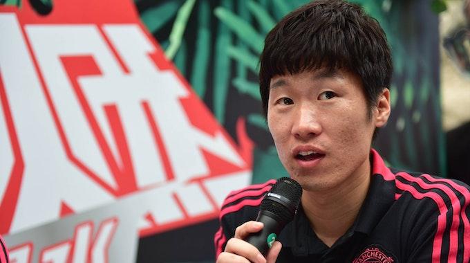 Ji-sung Park spricht in ein Mikrofon und trägt ein schwarz-rotes Shirt von Manchester-United.