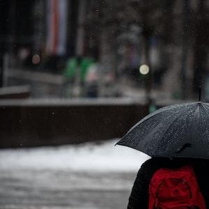 Düsseldorf: Ein Mann läuft mit Regenschirm durch den Regen in der Düsseldorfer Innenstadt.