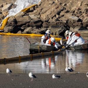 Einsatzkräfte errichten am 3. Oktober 2021 Ölbarrieren in der Nähe der Ortschaft Huntington Beach.