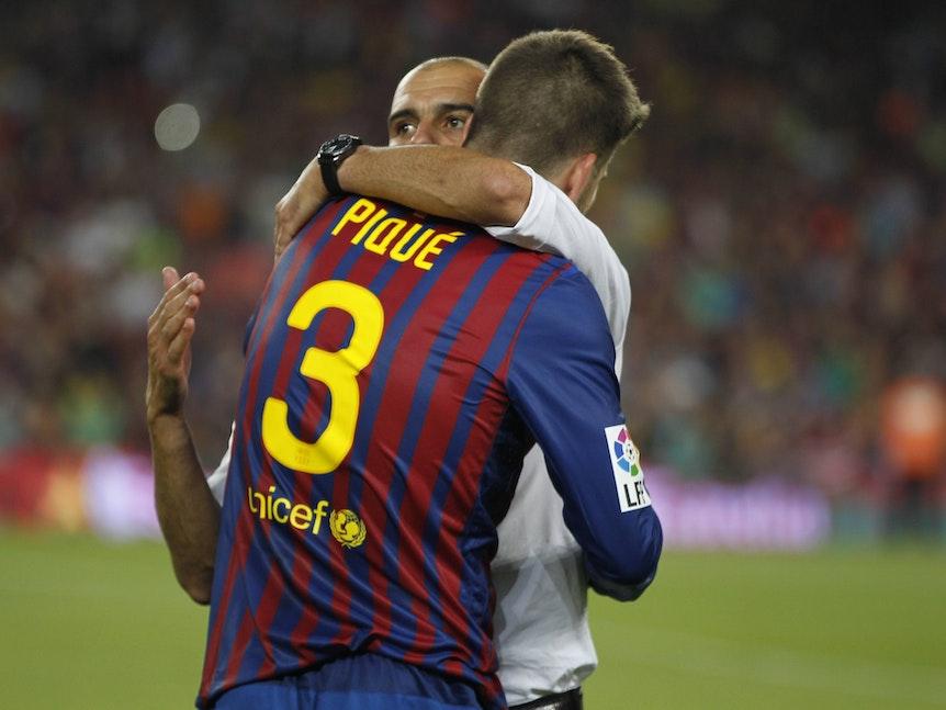 Pep Guardiola und Gerard Pique umarmen sich.