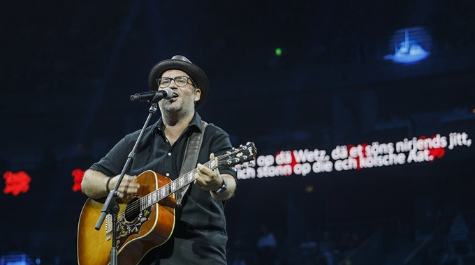 Björn Heuser spielt Gitarre und singt in der Lanxess-Arena.