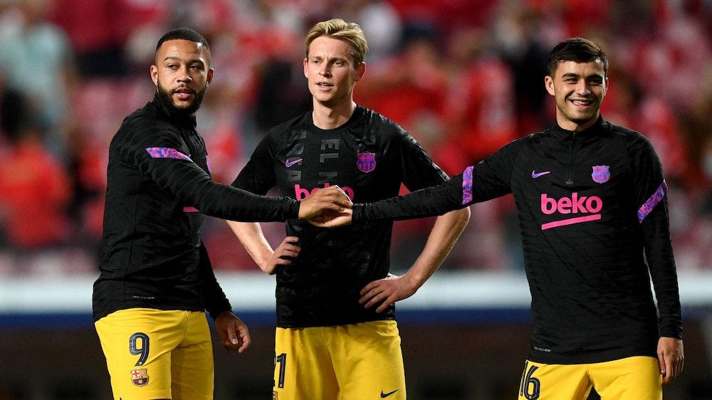 Die Barcelona-Stars Memphis Depay (l.), Frenkie De Jong und Pedri vor dem Champions-League-Spiel bei Benfica Lissabon am 29. September 2021.