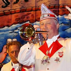 Helmut Blödgen spielt mit einer Hand Trompete, mit der anderen zählt er ein.