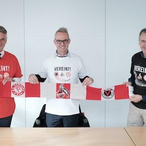 """Andreas Rettig, Alexander Wehrle und Hanns-Jörg Westendorf (v.r.) demonstrieren gemeinsam mit dem """"Mottoschal"""" und T-Shirt Einigkeit."""