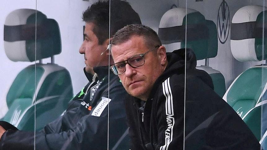 Gladbach-Manager Max Eberl, hier zu sehen am 2. Oktober 2021 beim Bundesliga-Duell seiner Borussia in Wolfsburg, hat in den kommenden Wochen und Monaten alle Hände voll zu tun. Eberl sitzt auf der Gästebank und blickt in die Kamera.
