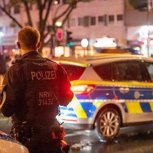 Ein Polizist einer Hundertschaft steht nachts neben einem Polizeiauto auf der Zülpicher Straße