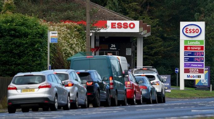 Autofahrer stehen vor einer Esso-Tankstelle Schlange, um zu tanken. In Großbritannien sind seit Montag (04.10.2021) Soldaten im Einsatz, um den anhaltenden Kraftstoffmangel an britischen Tankstellen einzudämmen.