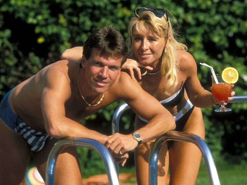 Lothar Matthäus und Sylvia stehen in Badekleidung am Pool. Lothar trägt Goldkette und Uhr, Sylvia hat eine auf den Kopf geschobene Sonnenbrille auf und einen Cocktail in der Hand.