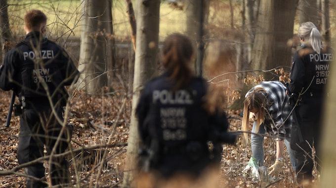 Polizeieinheiten durchsuchen einen Wald.