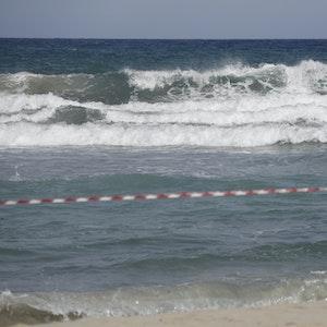 Ein Mann steht am abgesperrten Strand von Cala Mendia in Manacor auf Mallorca.