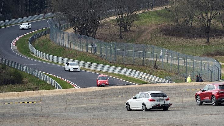 Das Symbolbild zeigt die Nordschleife des Nürburgrings im April 2021, mehrere Autos fahren auf der Strecke, einige Menschen stehen am Rand und schauen zu.