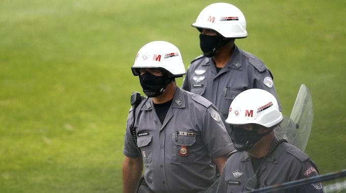 Drei uniformierte Militärpolizisten laufen über das Feld. Sie tragen Helme und Masken. Einer trägt ein Schild in der Hand.