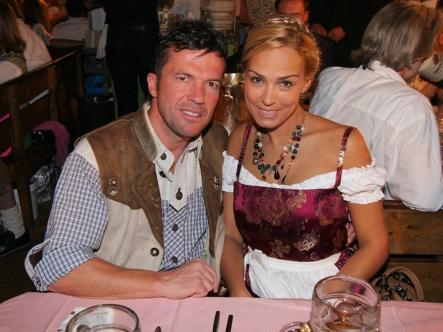 Lothar Matthäus und Frau Marijana sitzen im Festzelt am Tisch, vor ihnen stehen Maßkrüge.