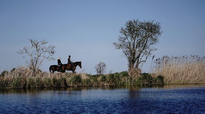 Im Sonnenschein passieren zwei Reiterinnen auf ihren Pferden einen See am Schulzendorfer Graben.