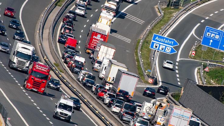Pkw und Lkw stauen sich auf der Autobahn A8 in Richtung Norden. Eine lange Schlange ist zu sehen.