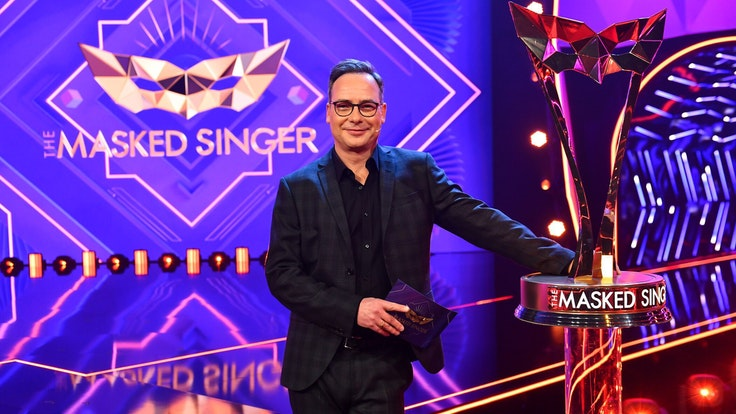 """""""The Masked Singer""""-Moderator Matthias Opdenhövel steht auf der Show-Bühne neben der Sieger-Trophäe."""