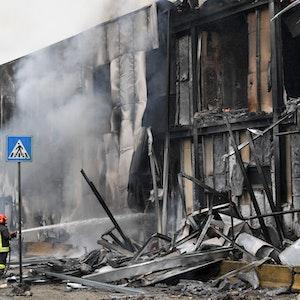 Ein Kleinflugzeug stürzt in Mailand am Sonntag (3. Oktober) nur Augenblicke nach dem Start ab und in ein Bürogebäude. Feuerwehrleute löschen die Trümmer des Gebäudes, Qualm steigt auf.