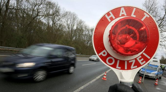Ein Polizist winkt am 21.03.2017 auf der Autobahn 555 bei Köln (Nordrhein-Westfalen) Fahrzeuge zur Kontrolle raus.
