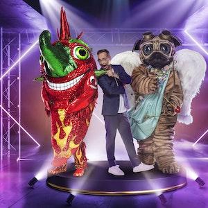Zwei der neuen Kostüme bei The Masked Singer 2021 stehen neben Moderator Matthias Opdenhövel.