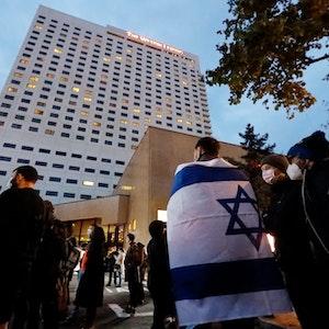 Ein Demonstrant trägt die Fahne Israels über den Schultern. Nach Antisemitismus-Vorwürfen haben sich am Abend Hunderte Menschen vor dem «Westin Hotel» Leipzig versammelt, um Solidarität mit dem Musiker Gil Ofarim und Jüdinnen und Juden in Deutschland zu zeigen.