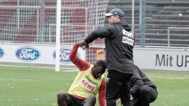 Steffen Baumgart hilft dem angeschlagenen Kingsley Schindler im Training des 1. FC Köln auf die Beine.