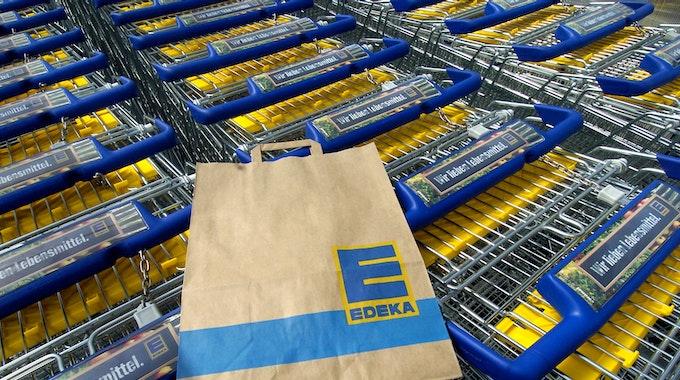 Eine Edeka-Tüte liegt auf einem Einkaufswagen. Die Supermarktkette ruft Sangria zurück. Verkauft wurde das alkoholische Getränk auch in Nordrhein-Westfalen.