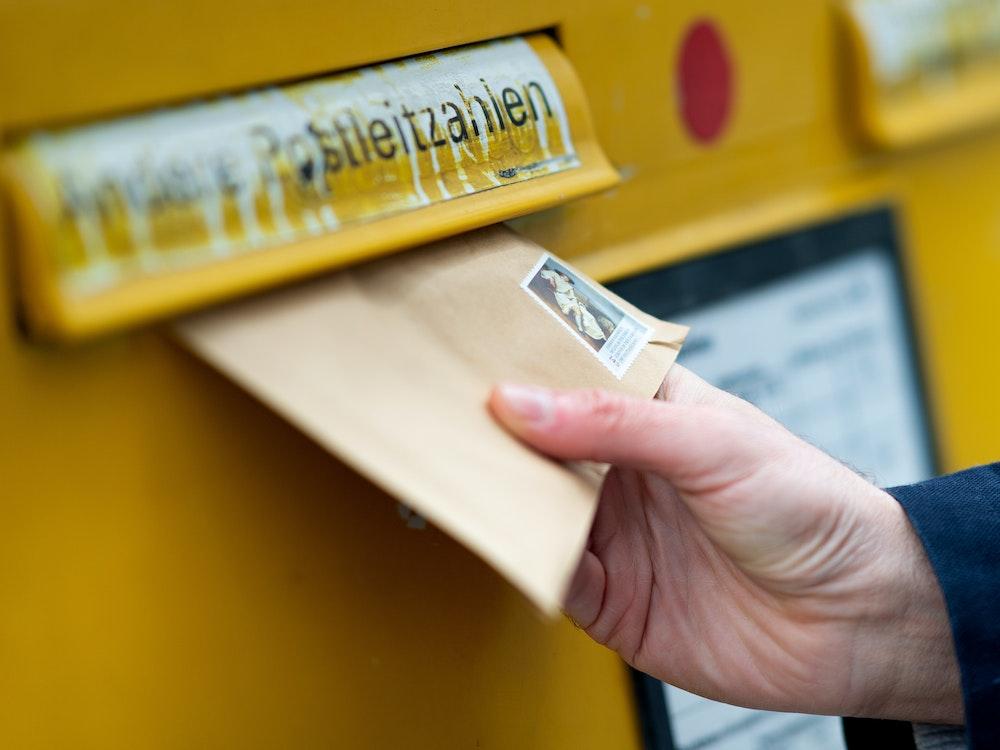 Das Symbolbild zeigt einen Mann, der einen Brief in einen Briefkasten wirft.