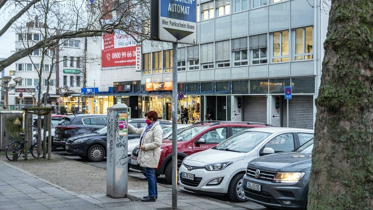 Eine Frau zeiht in Duisburg einen Parkschein.