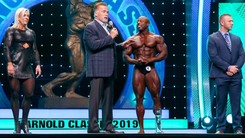 Arnold Schwarzenegger interviewt George Peterson auf der Bühne