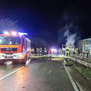 Feuerwehrleute stehen neben dem ausgebrannten Laster auf der Autobahn.