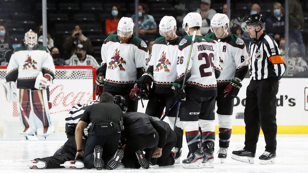 Die Spieler der Arizona Coyotes versammeln sich bei einem NHL-Vorbereitungsspiel um den am Boden liegenden Schiedsrichter Ryan Gibbons, der von Medizinern behandelt wird.