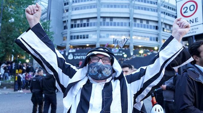 Ein Fan von Newcastle trägt eine arabische Kopfbedeckung und streckt die Arme zum Jubeln in die Höhe.