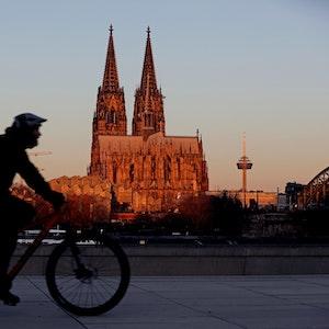 Ein Radfahrer fährt am Morgen am Dom vorbei, der von der aufgehenden Sonne angeleuchtet wird.