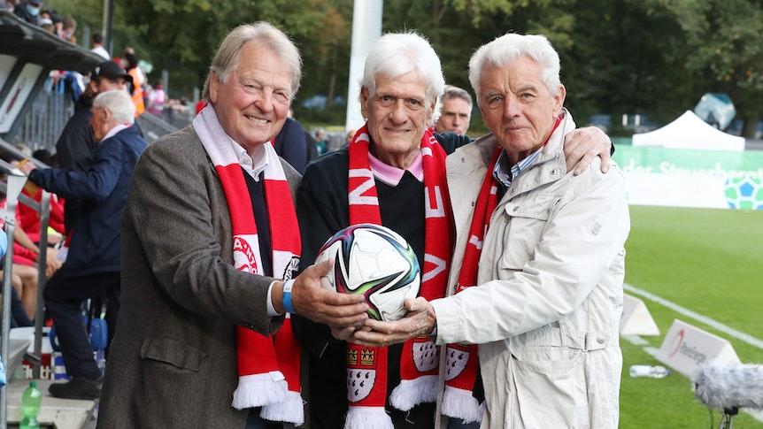 Karl-Heinz Thielen, Wolfgang Fahrian und Erich Ribbeck stehen vor der Tribüne.