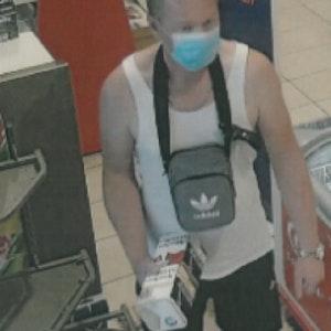 Mann in einem Verkaufsraum mit Mundschutz und Unterhemd